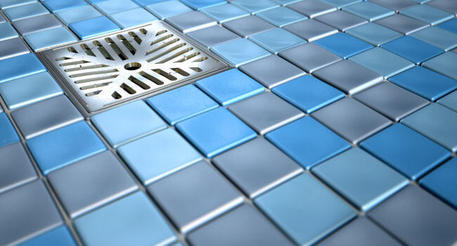 Shower floor made of small square tiles in various shades of blue