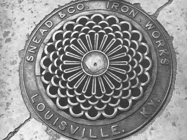 """Close up of a sewer grate that reads """"Snead & Co Iron Works Louisville KY"""""""