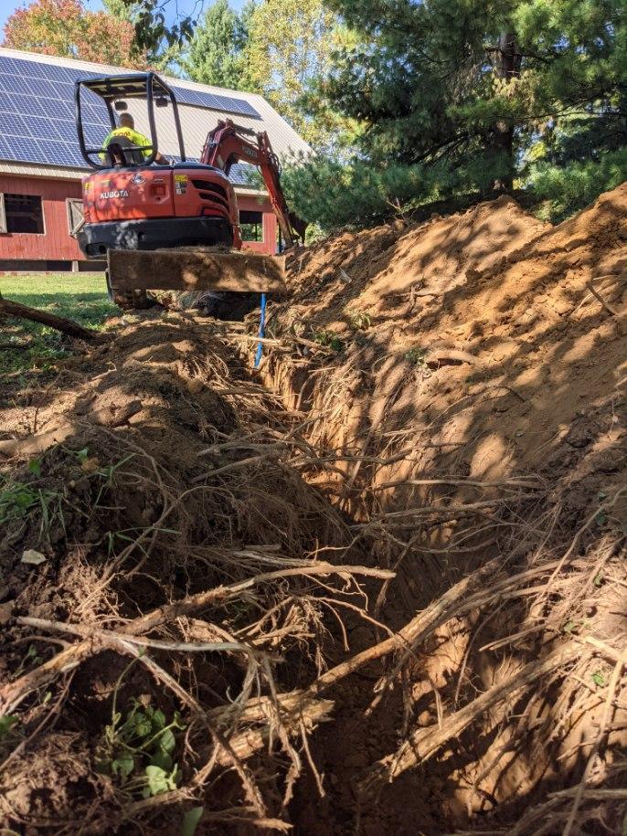 Backhoe digging up a water line